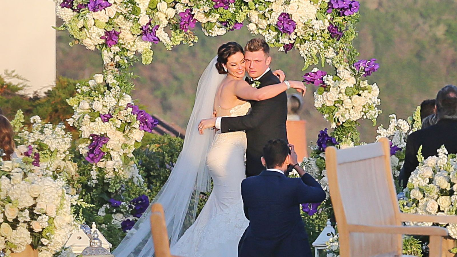 An image of Nick and Lauren Carter on their wedding, embracing under an arch of purple and white flowers. Lauren is smiling and wearing a beautiful white wedding dress and Nick Carter looks to be moved to tears as they both look at a photographer in front of them.