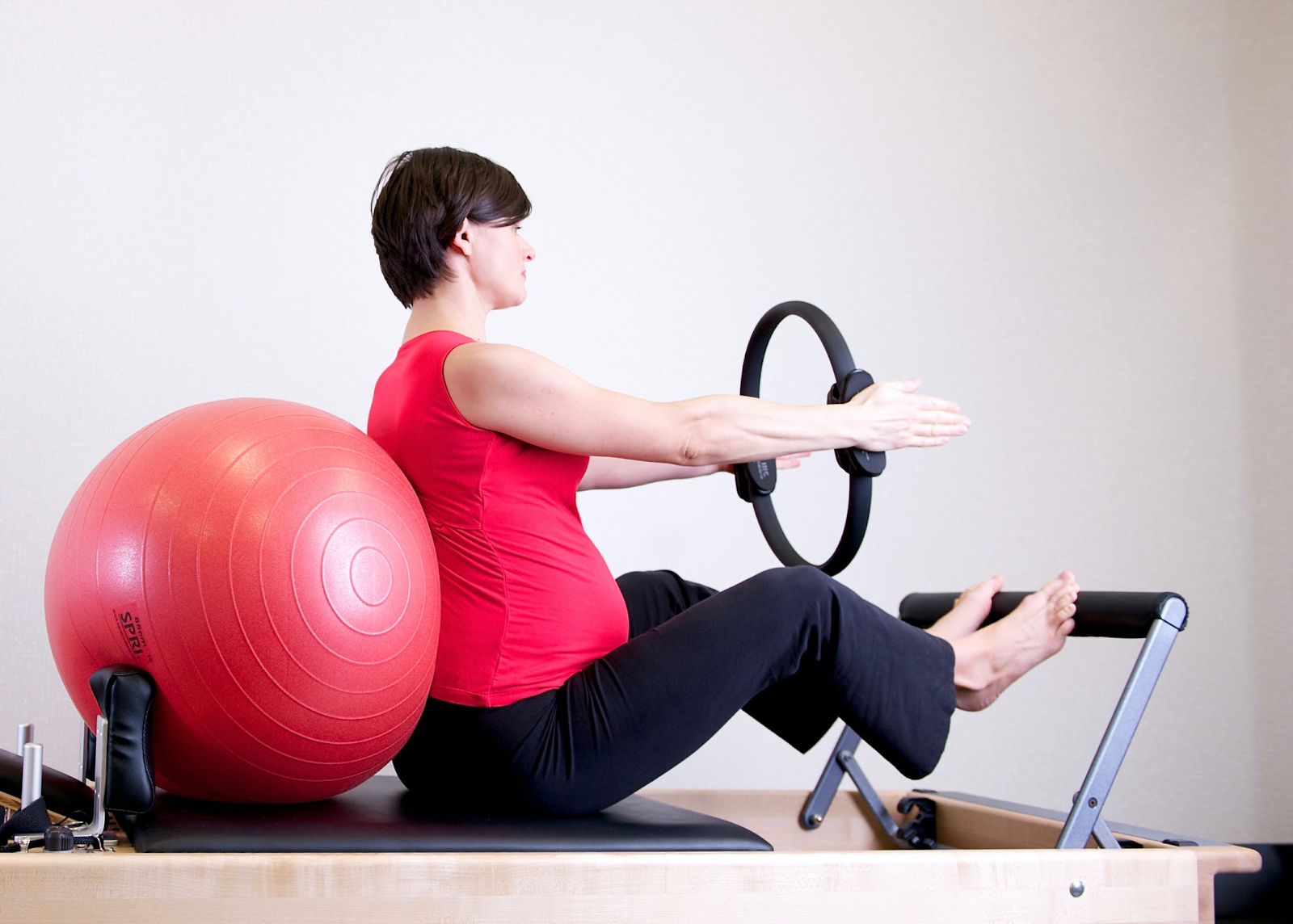 An image of a pregnant woman wearing red leaning up against a red exercise ball. She is resting her feet on an elevated bar and is holding a black ring between her arms.