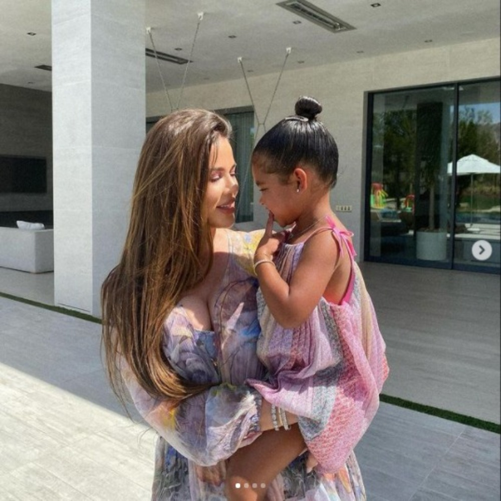Khloé Kardashian poses with her daughter True in her arms. The two look at each other and Kardashian smiles. They are wearing matching gauzey dresses with lilac, yellow, and pink colors throughout the garment. The pair are in front of a large outdoor porch space.
