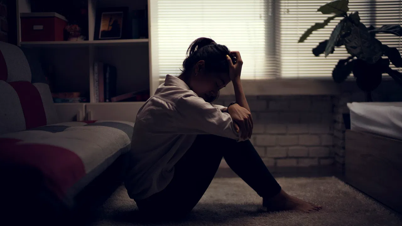 An image of a woman sitting in the dark with her knees pulled close to her chest, a hand on her head and staring at the floor with a sad expression on her face.