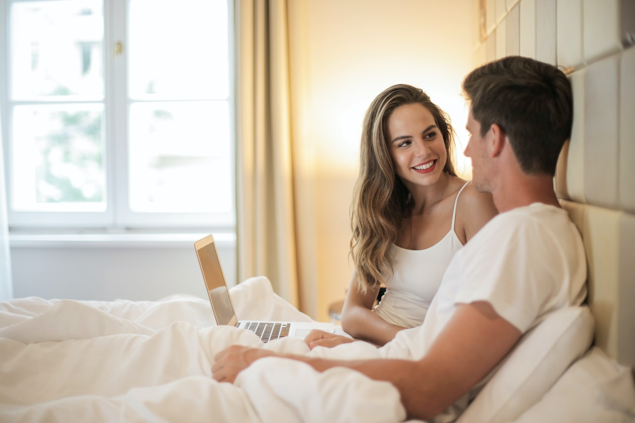 A man and a woman in comfortable clothing lay in bed together. The pair smile at each other and the woman holds a laptop on her lap.