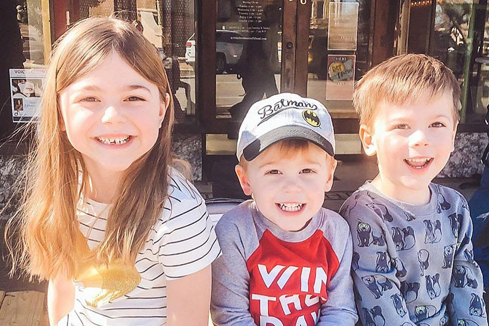 The three Smith children, smiling for the camera outside of a restaurant or store