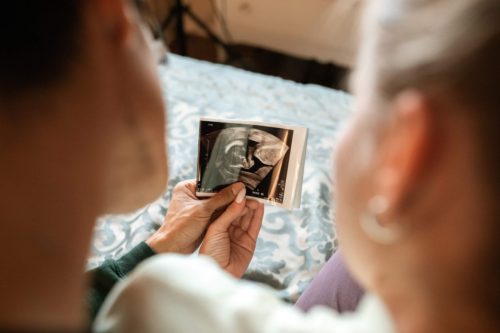 A couple, faces unseen, together holding ultrasound pictures