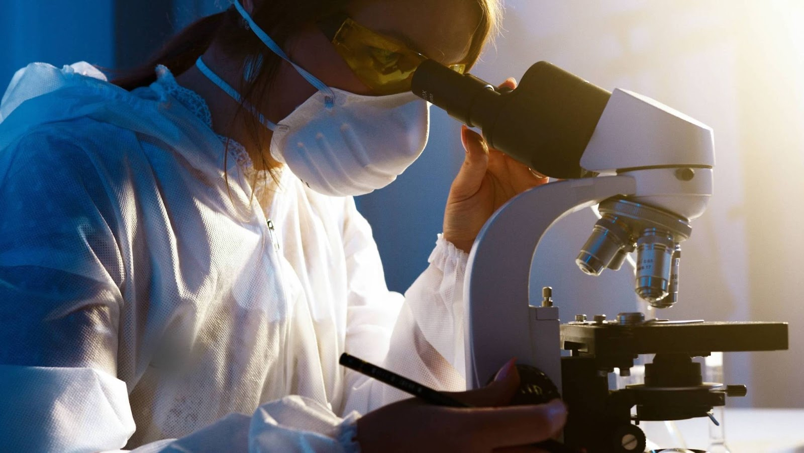 Scientist wearing PPE inspects unidentified object through microscope