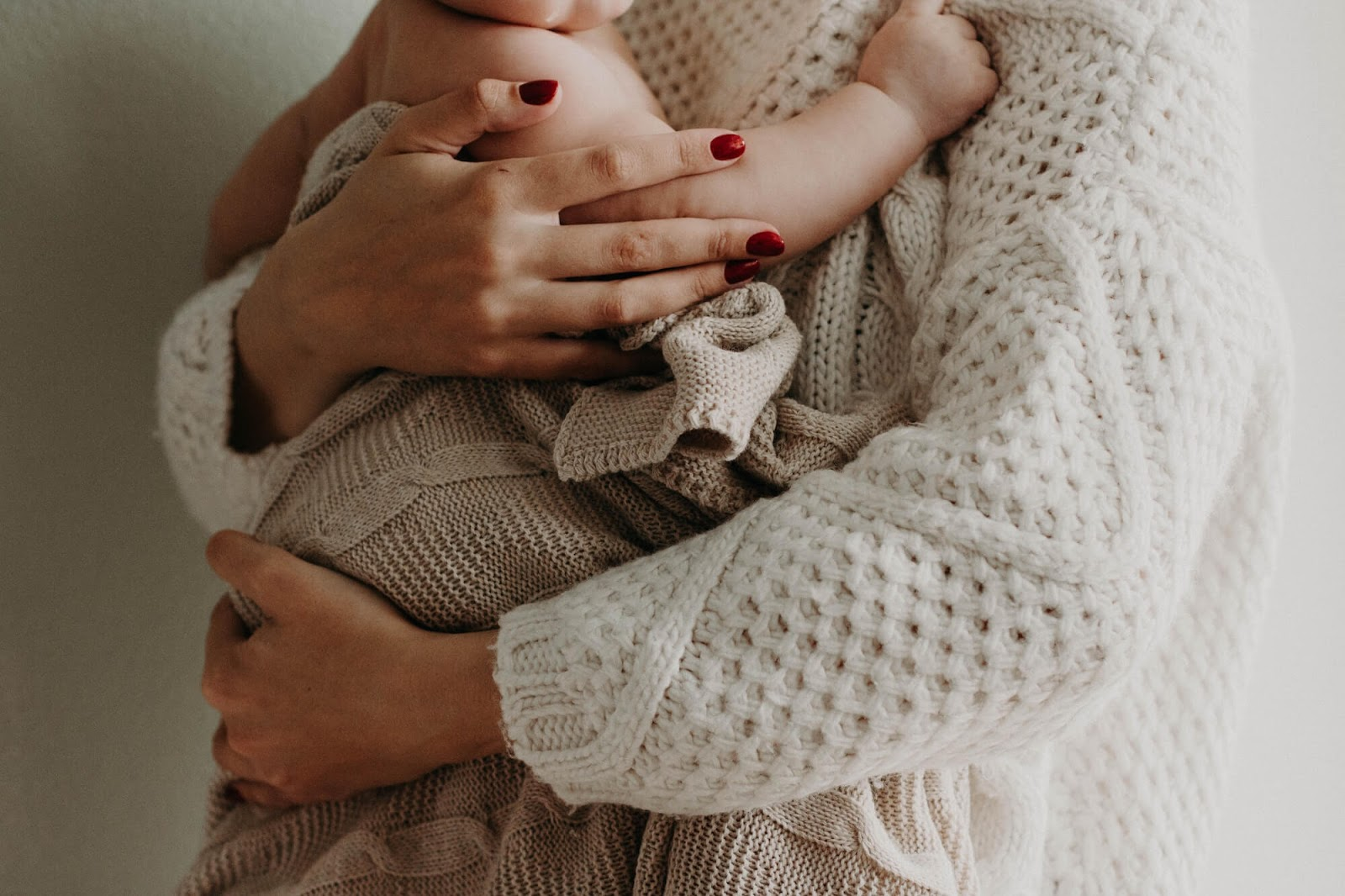 A mother holds her baby to her torso. She is in a white sweater and the baby is in a beige blanket. Their faces are unseen