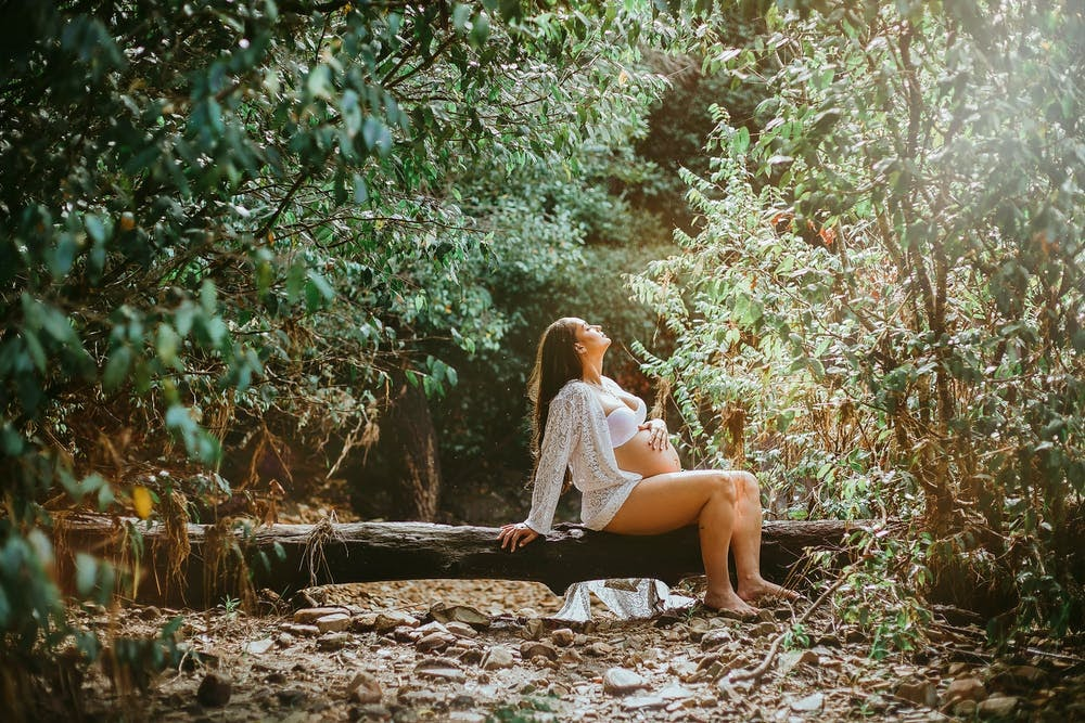 A pregnant woman sits on a fall tree trunk in the woods. She is holding her stomach with one hand while she leans o the other and is looking at the sky with her eyes closed.