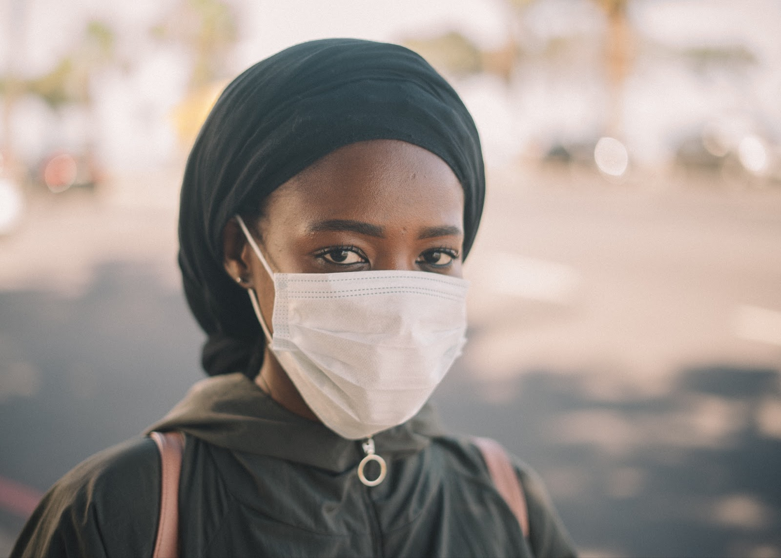 A young girl is the enter of the photo as the background is blurred. She wears all black, a head wrap, and a white surgical mask as she looks at the camera.