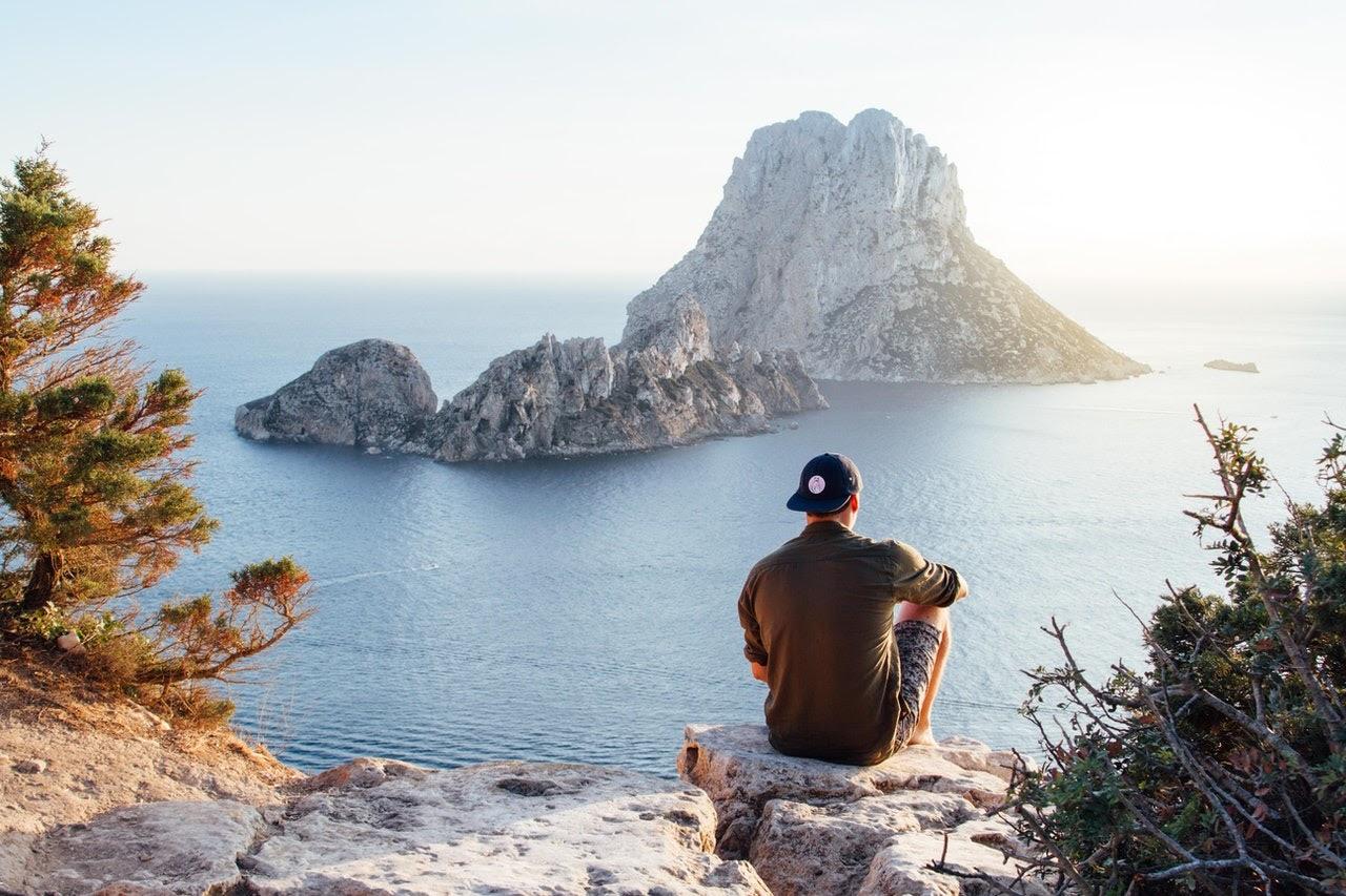Man sitting and facing water