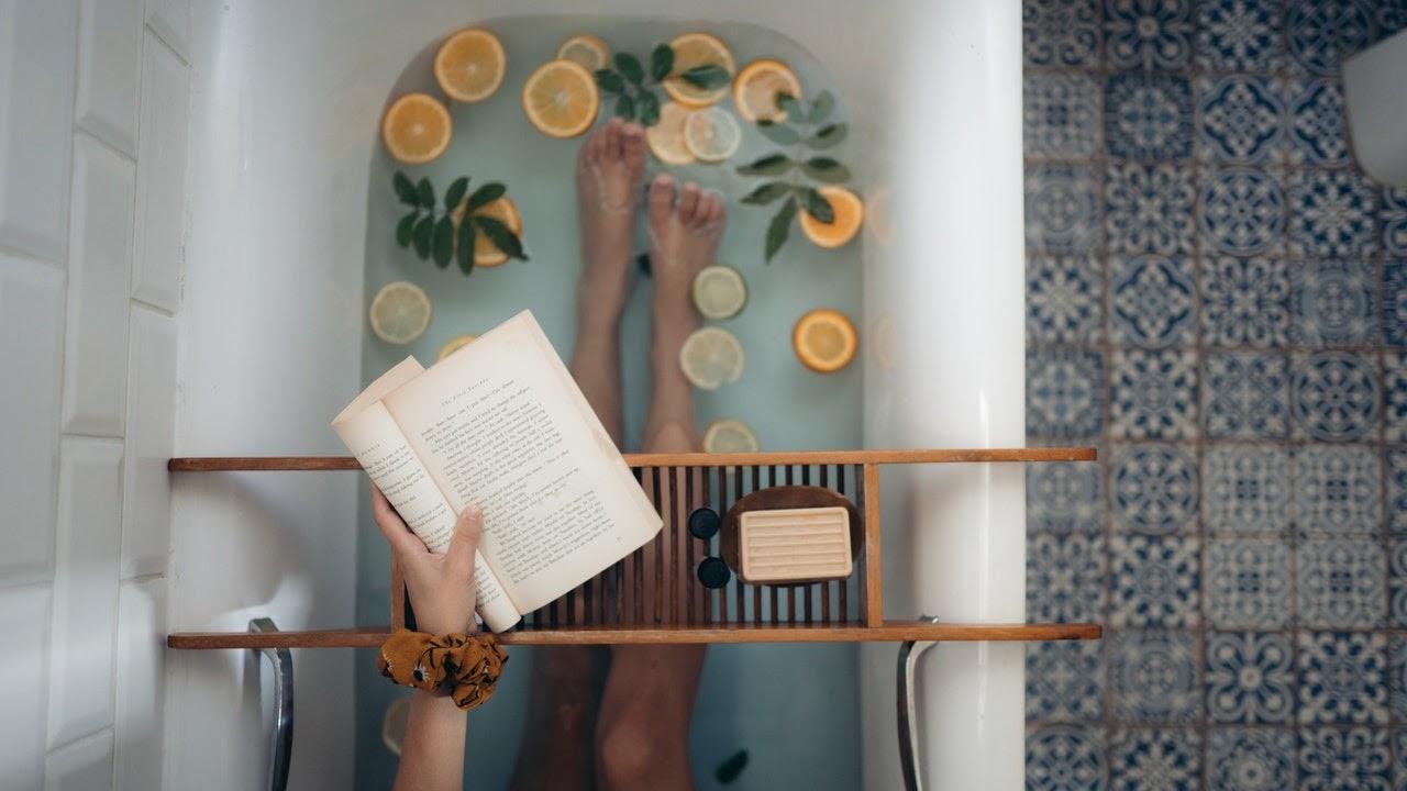 Woman sitting in bath reading book