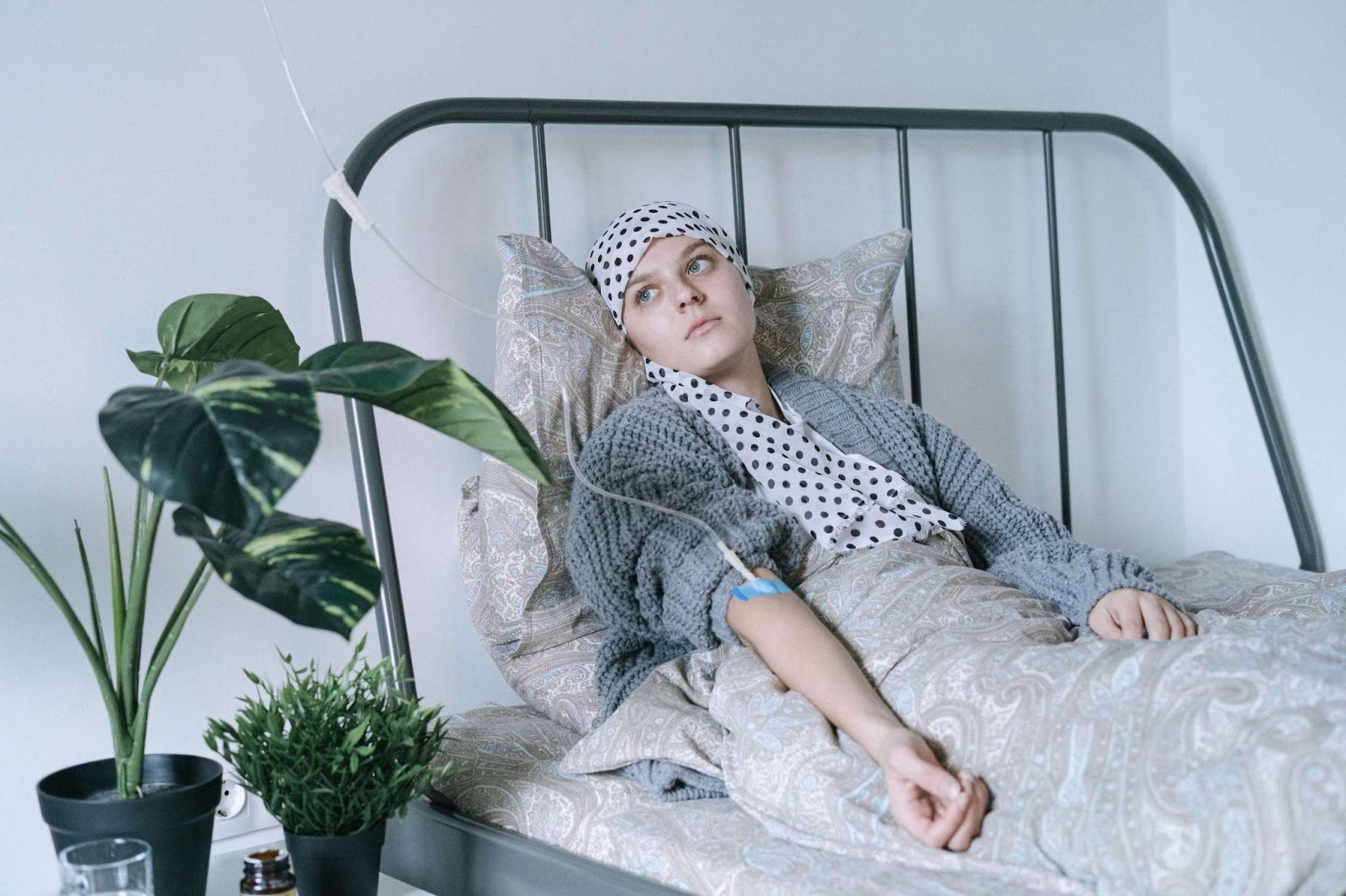 A female cancer patient, lying in bed with an IV in her arm, looking at a window out of frame