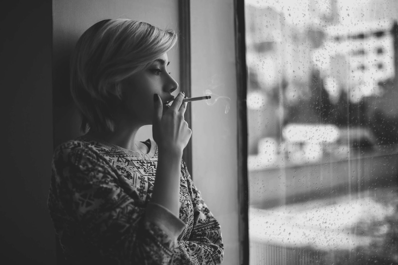 black and white photo of a blonde woman staring out the window at a rainy city as she smokes a cigarette