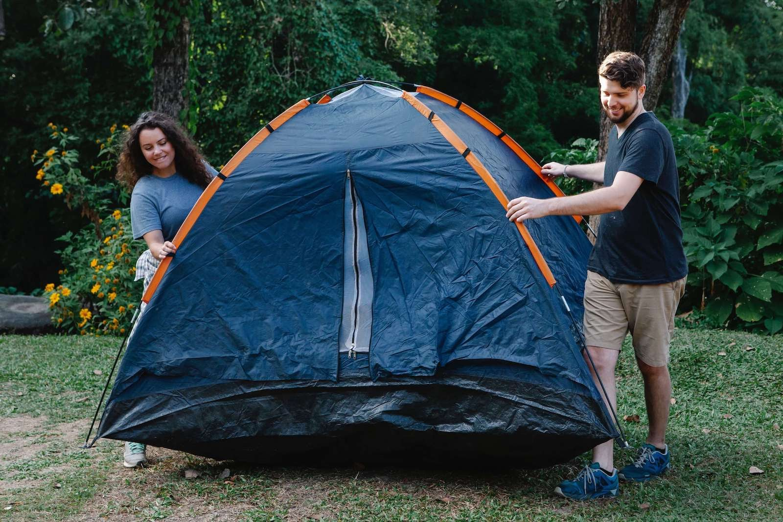 A couple setting up a tent in the grass