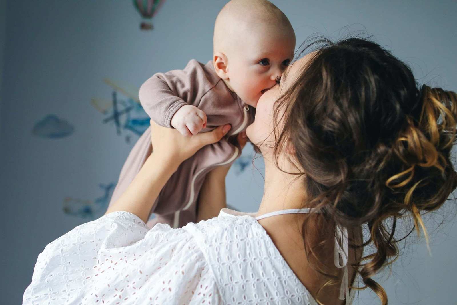 A young mother embraces her healthy baby