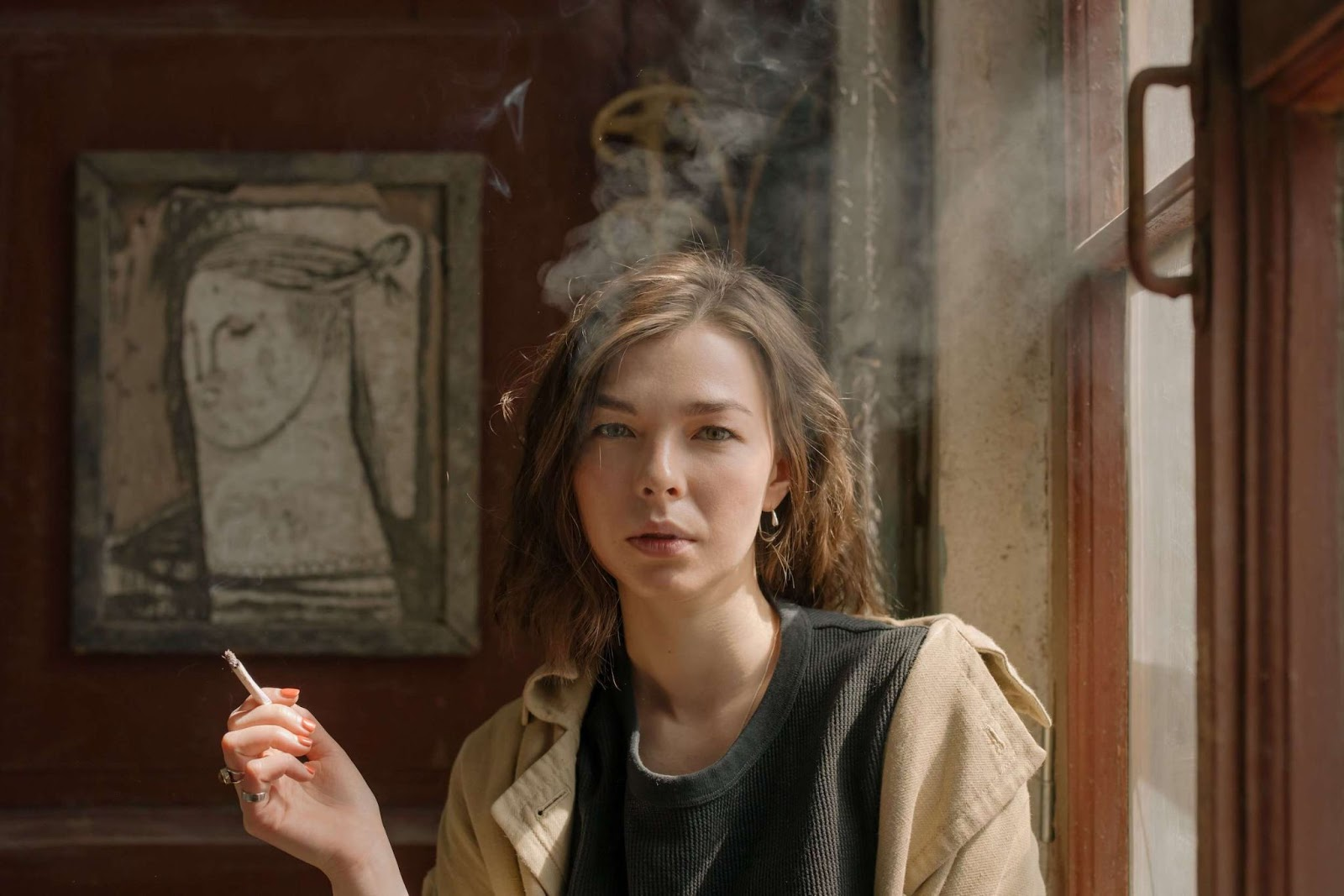 A woman smoking and looking directly into camera, the smoke swirling around her head in the light of the nearby window