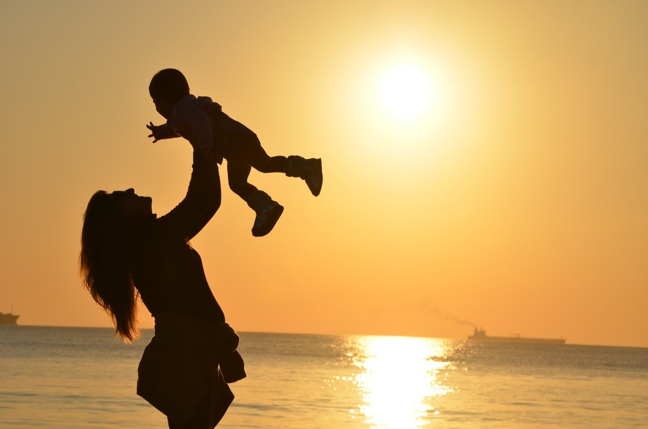 Mother playing with child at beach