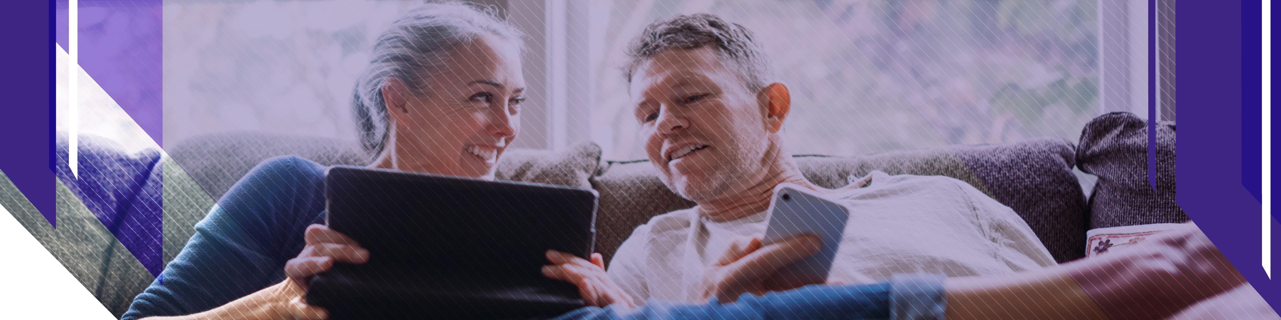 Couple sitting on sofa looking at tablet