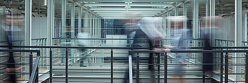 Abstract photo depicting the rapid movement of office personnel in a high speed office environment