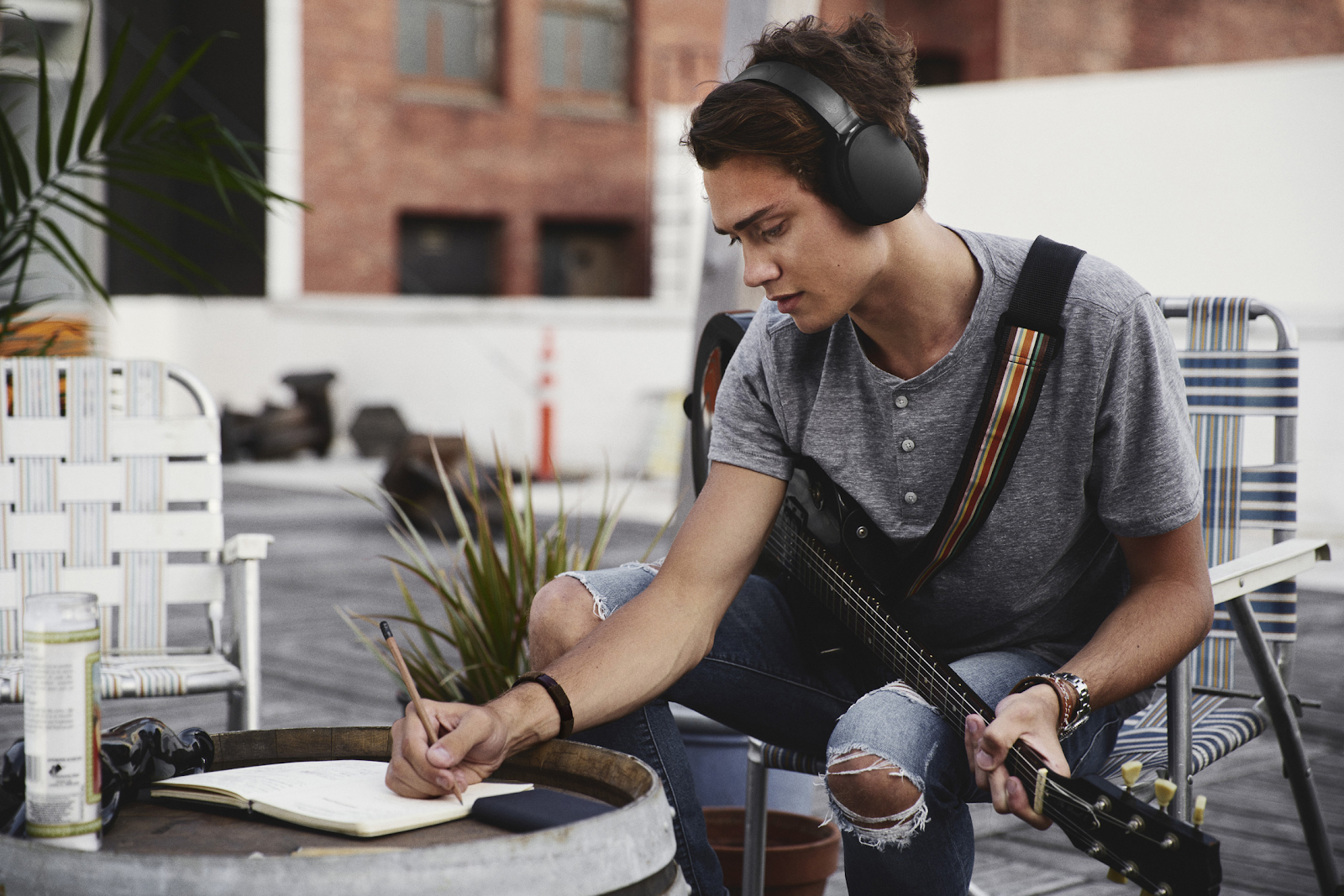 man with a guitar and wireless headphones writing in a notebook