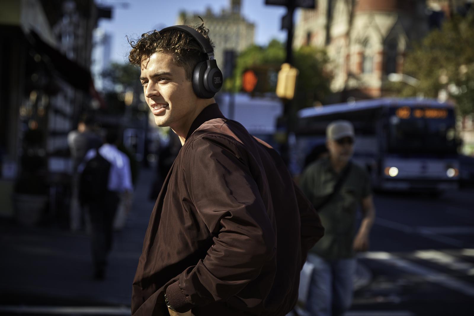 man walking down street wearing JBL wireless over the ear headphones
