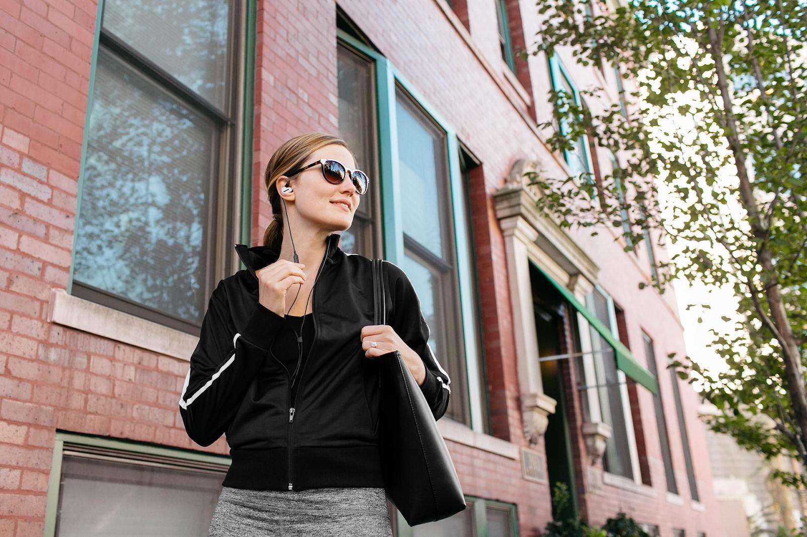 woman walking down street wearing shure se425 in ear headphones