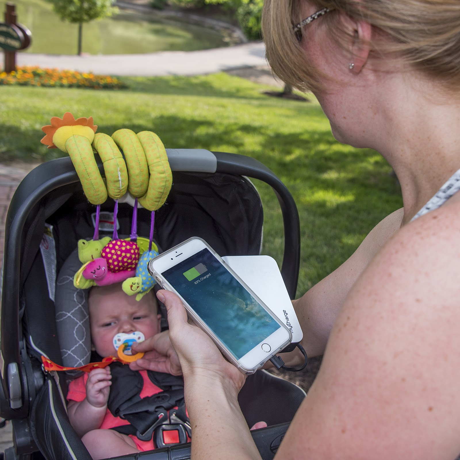 woman charging iphone while taking care of baby