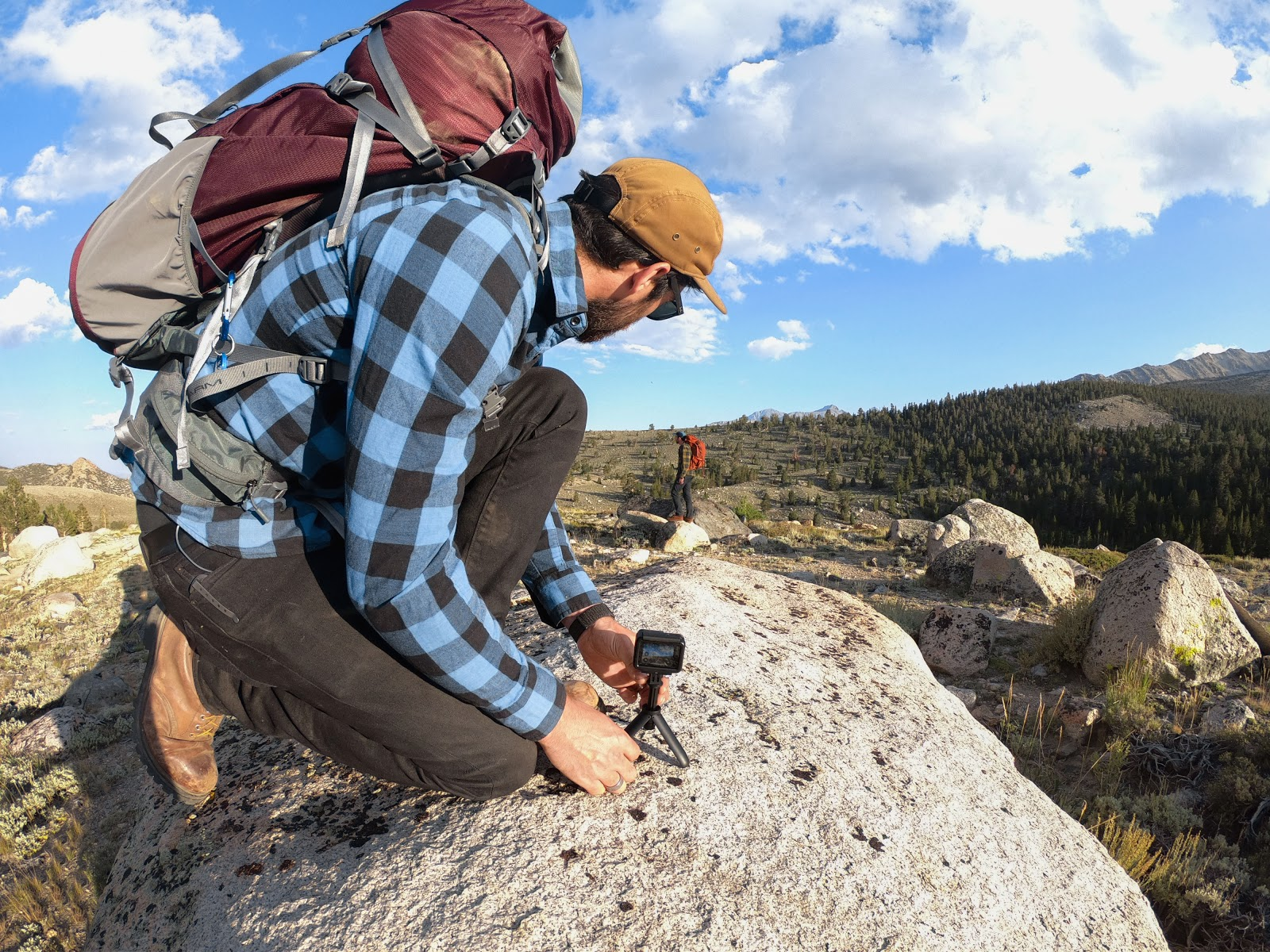 man setting up gopro on a rocky hill