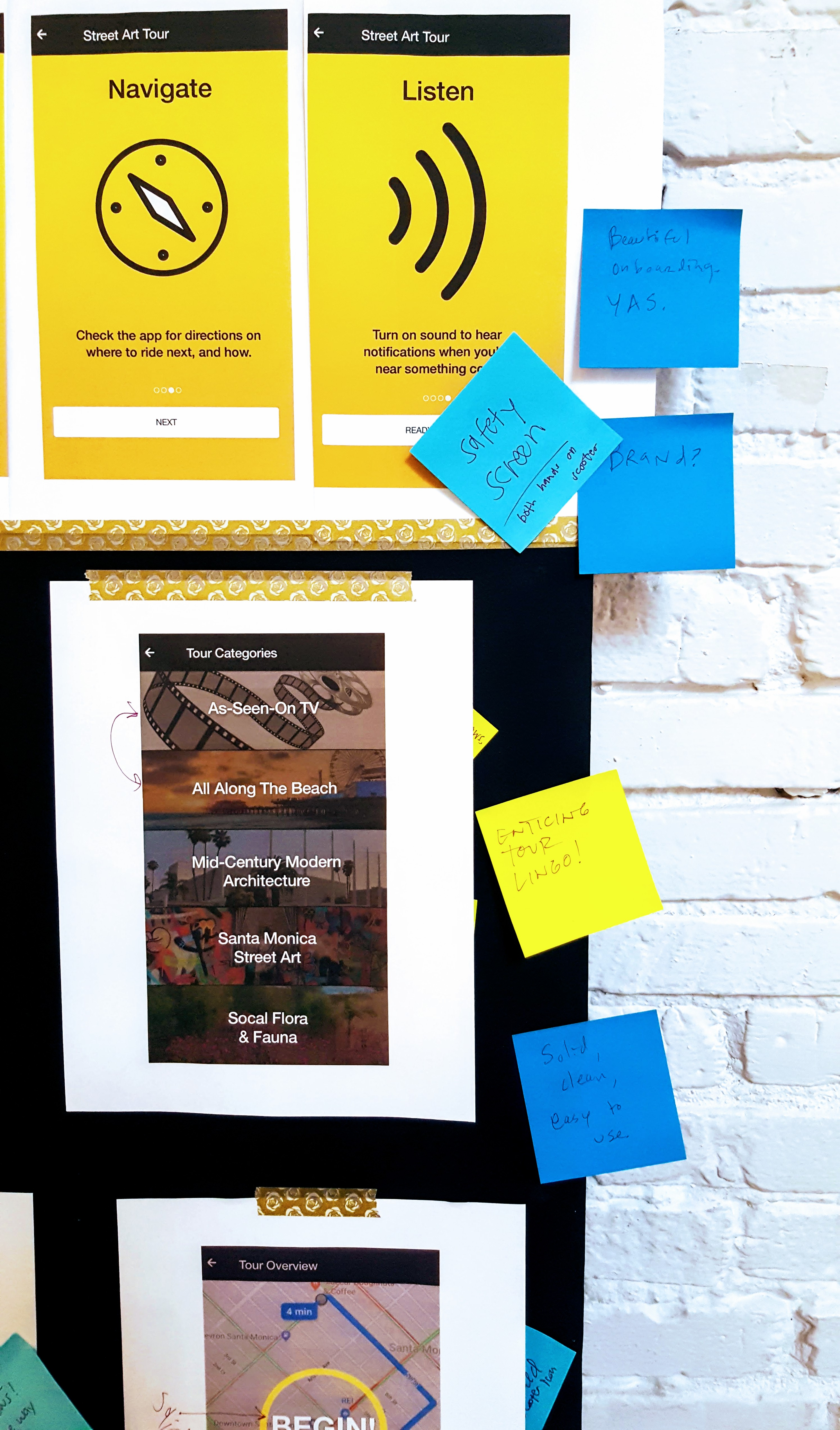Full-color mockup print-outs taped to a black board and decorated with post-its commenting on the mockup design