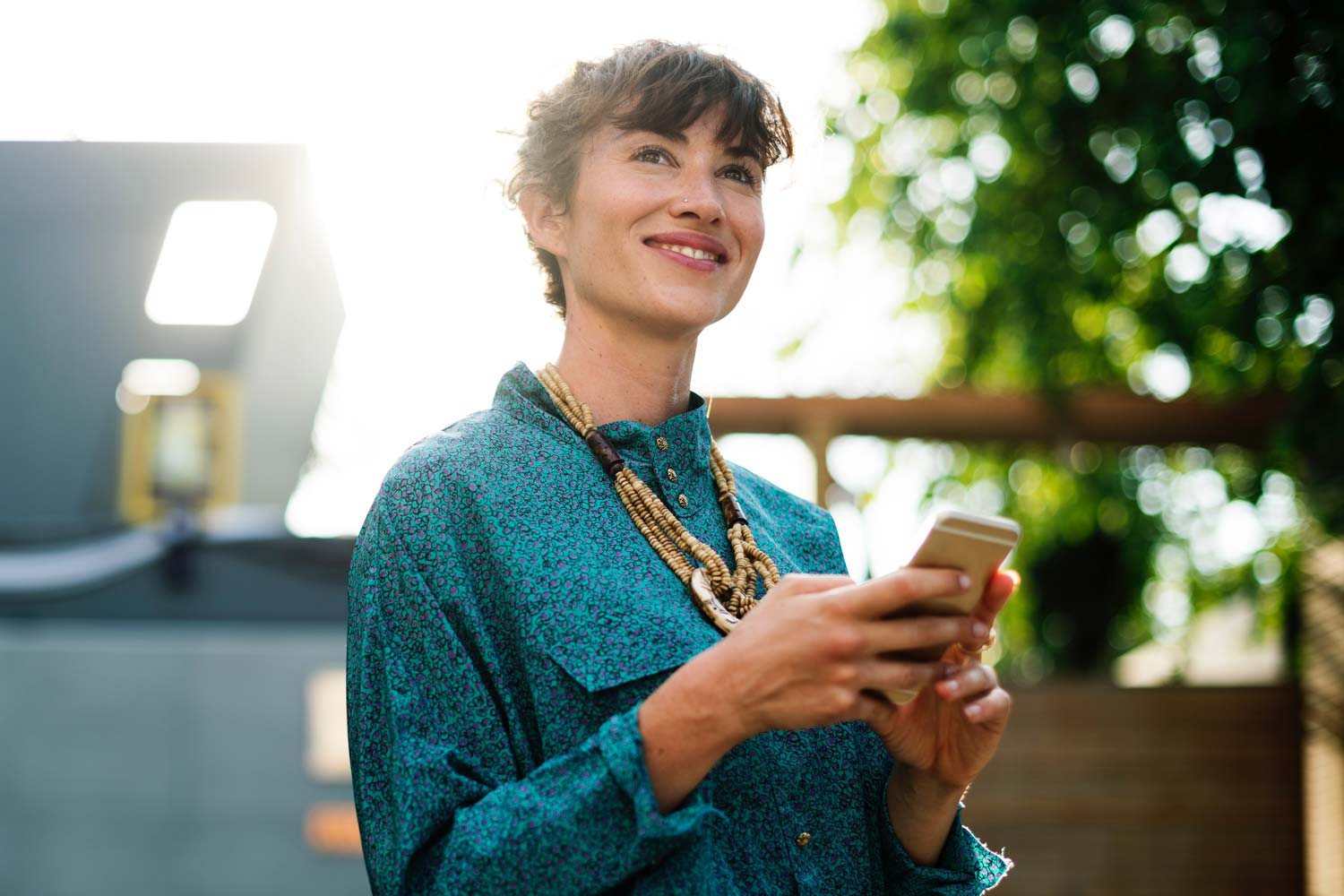 Young, smiling woman gazing thoughtfully up from her smartphone