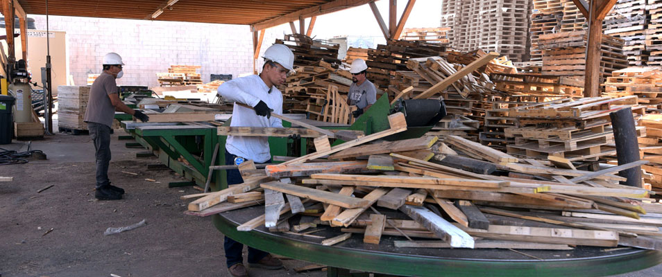 workers breaking apart pallets