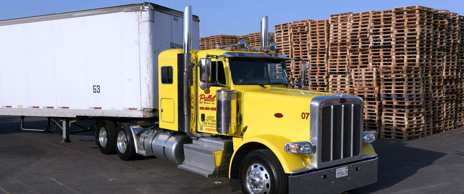 yellow big rig in front of pallets
