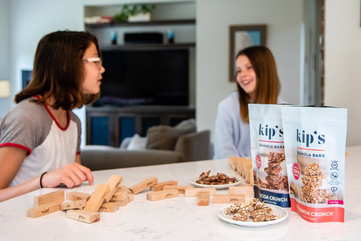 Two girls playing Jenga and eating Kip's