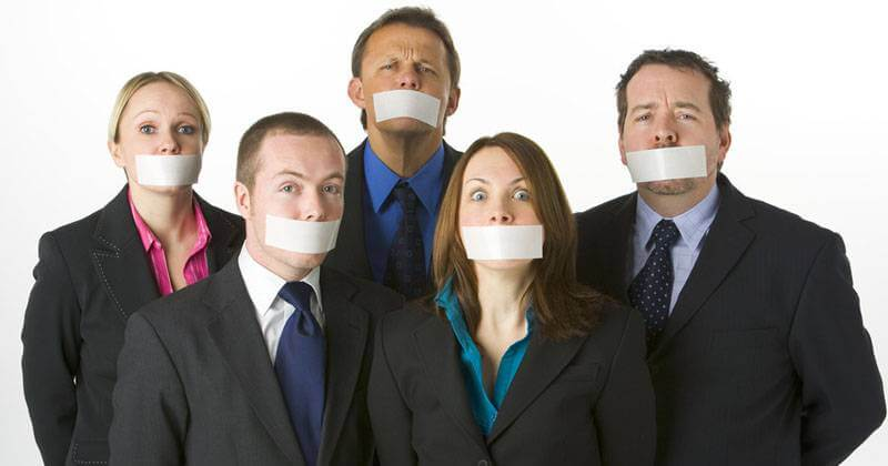 Employees comically exercising silence with mouth tape