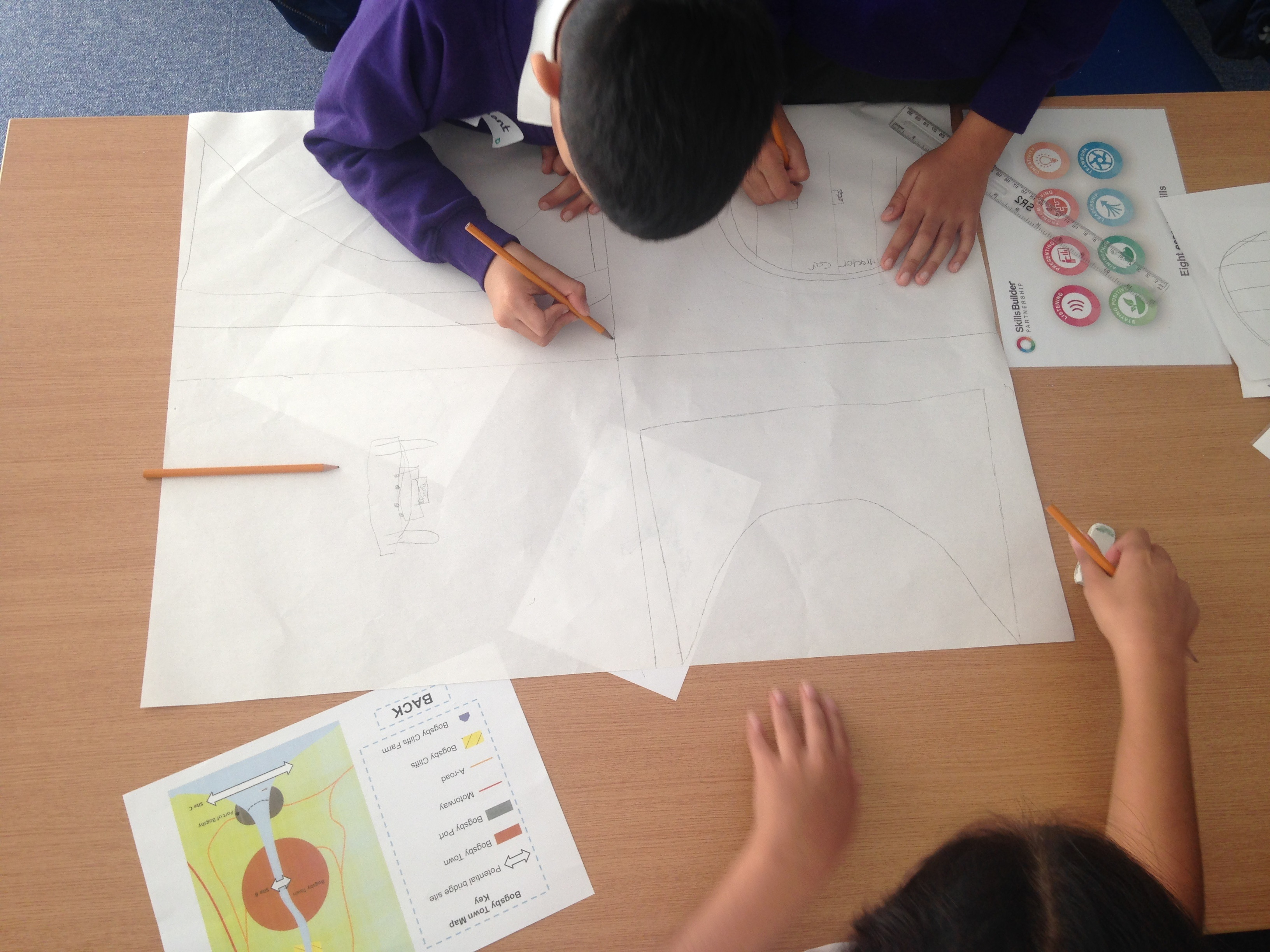 All hands on deck for drawing their architectural bridge designs as a team.