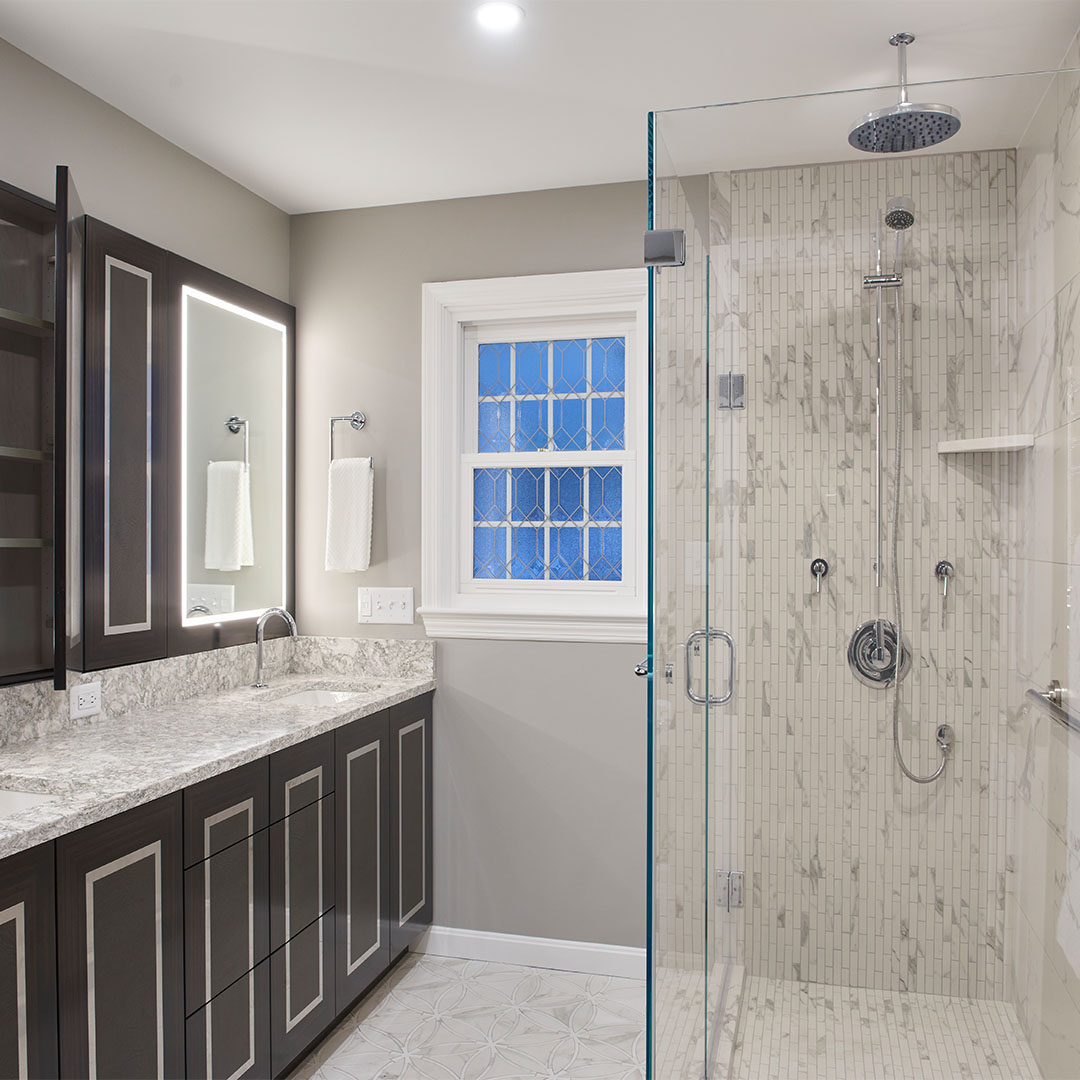 remodeled bathroom with custom cabinetry and glass tile shower