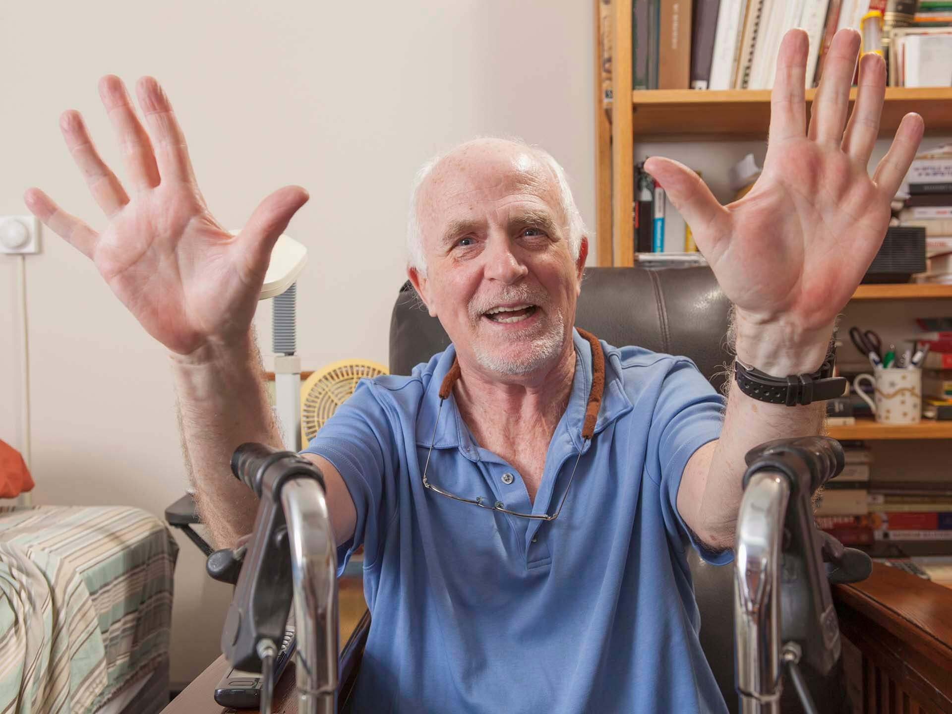 A smiling elderly man sits in front of his walker with his hands in the air.