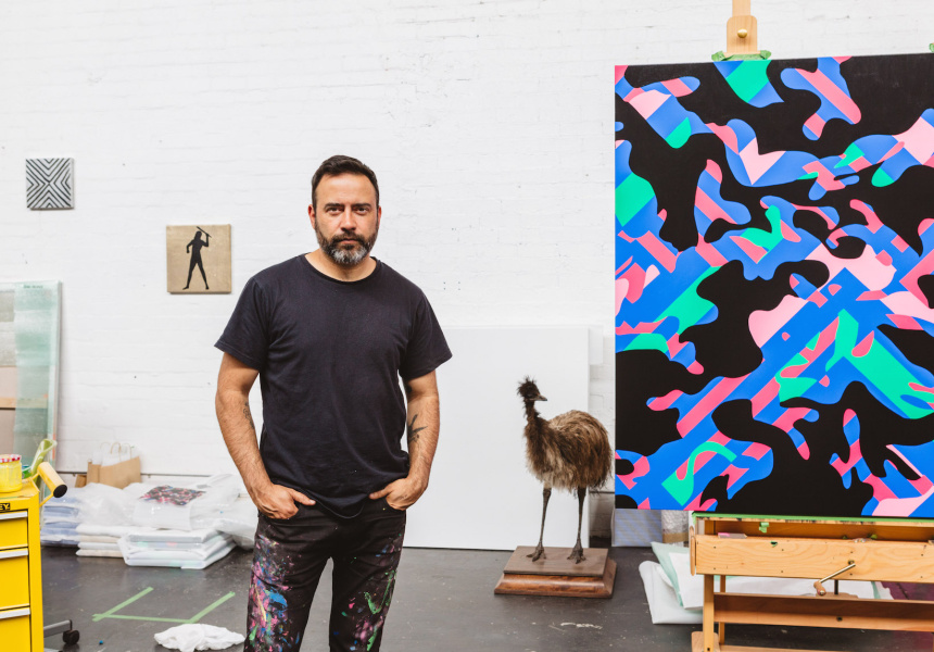 Reko Rennie standing in front of a painting in his studio