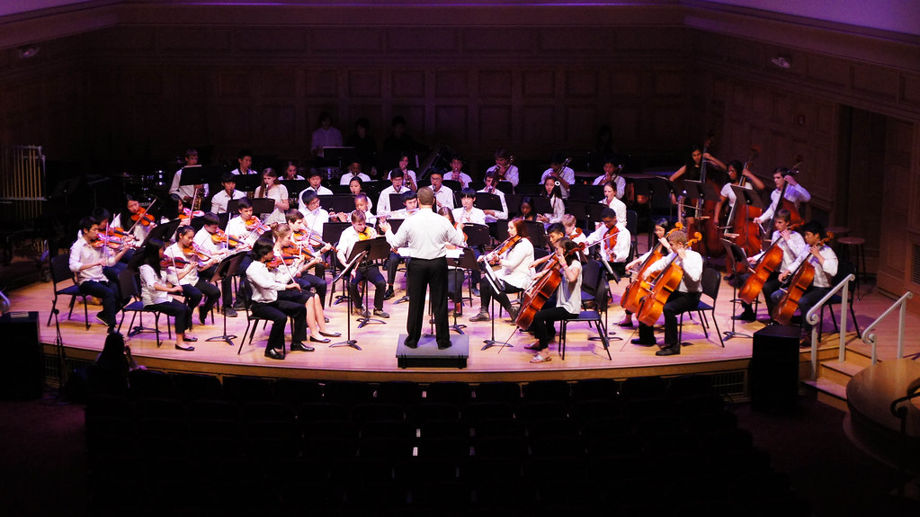 School orchestra with conductor on stage