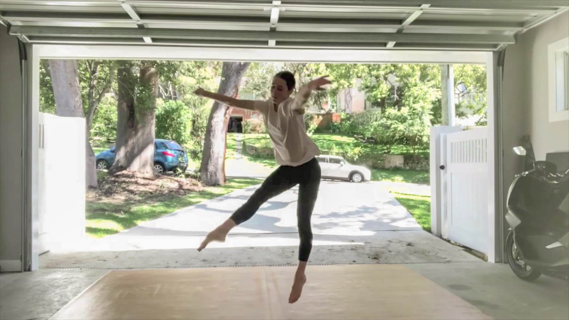A student at home in her garage leaping backwards, with arms out and right leg pointed forwards.
