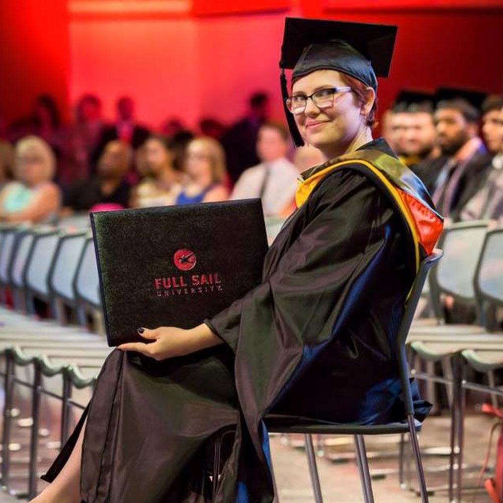 Me at my Master's graduation holding my diploma