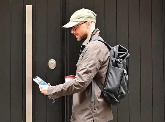 Man using his phone to unlock a door
