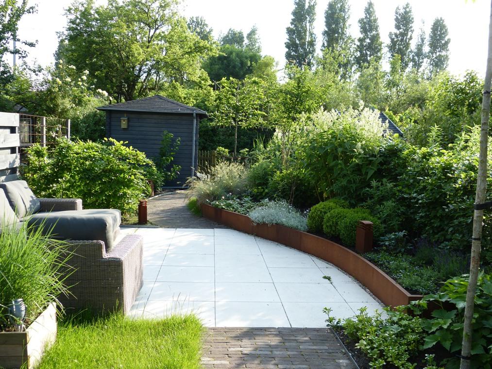 De ronde vorm van de verhoogde border leidt de blik verder de tuin in.