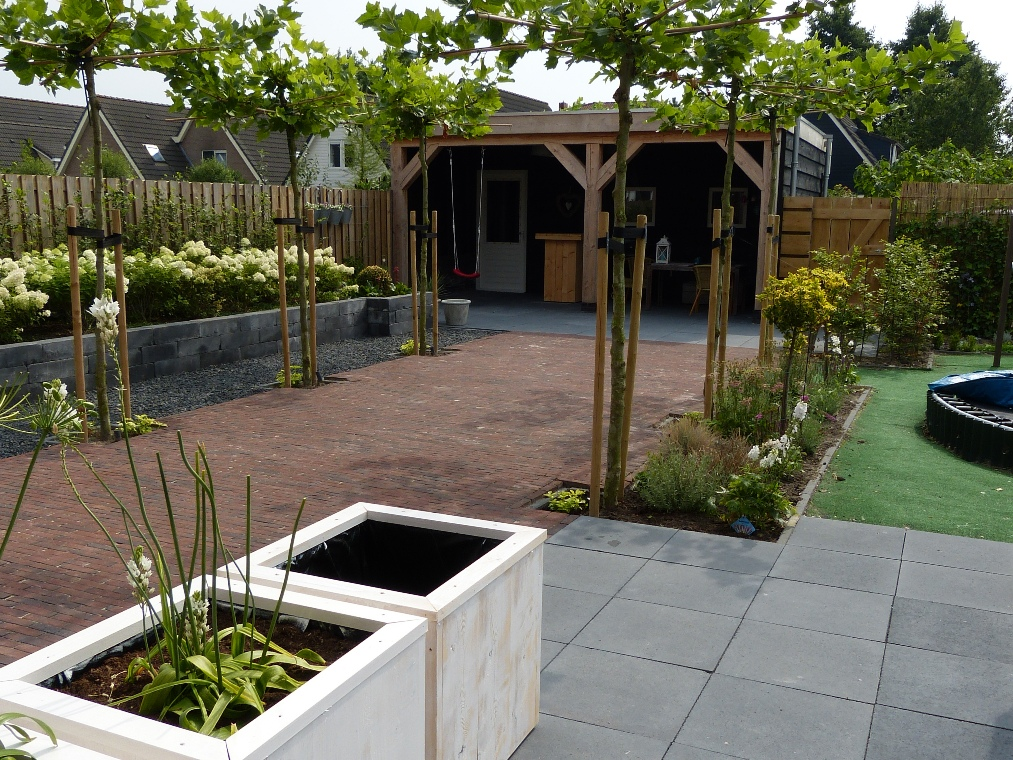 Een moderne tuin met een landelijke look in stompetoren for Ontwerp voortuin met parkeerplaats