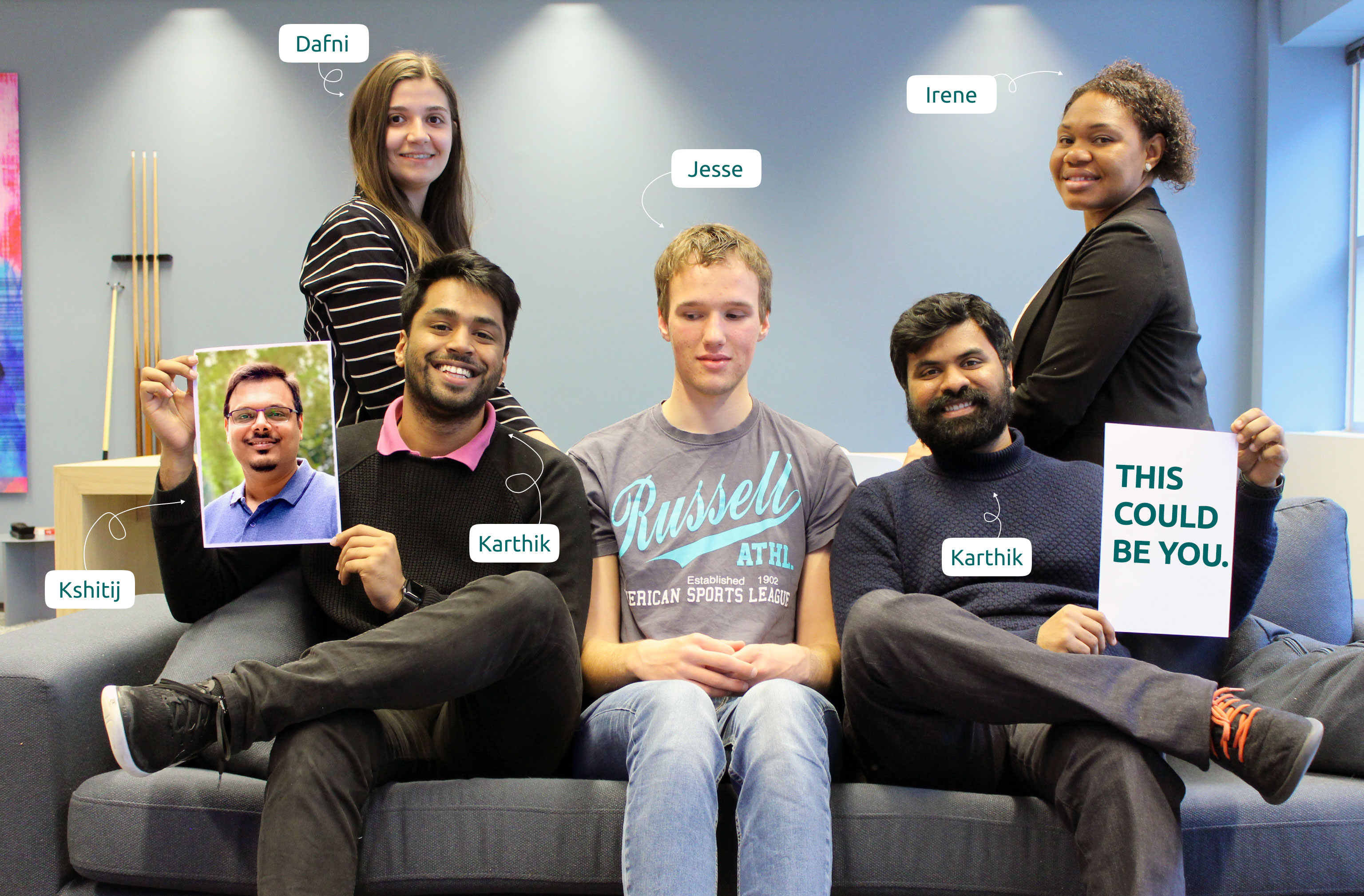 "Team Envision looking cheerful, with Karthik, Jesse and Karthik sitting on a couch, and Dafni and Irene standing behind them. Karthik is holding a picture of Kshitij in one hand and the other Karthik is hold a paper saying ""This could be you."""
