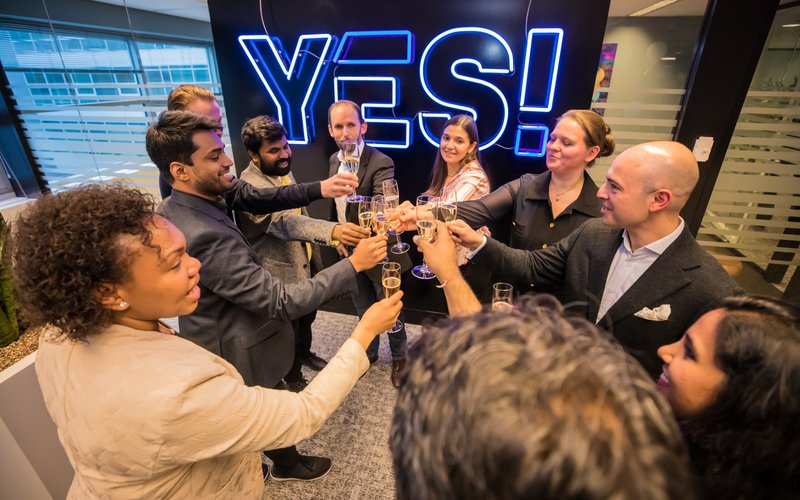 The whole Envision team celebrating milestone with some champagne in their hands