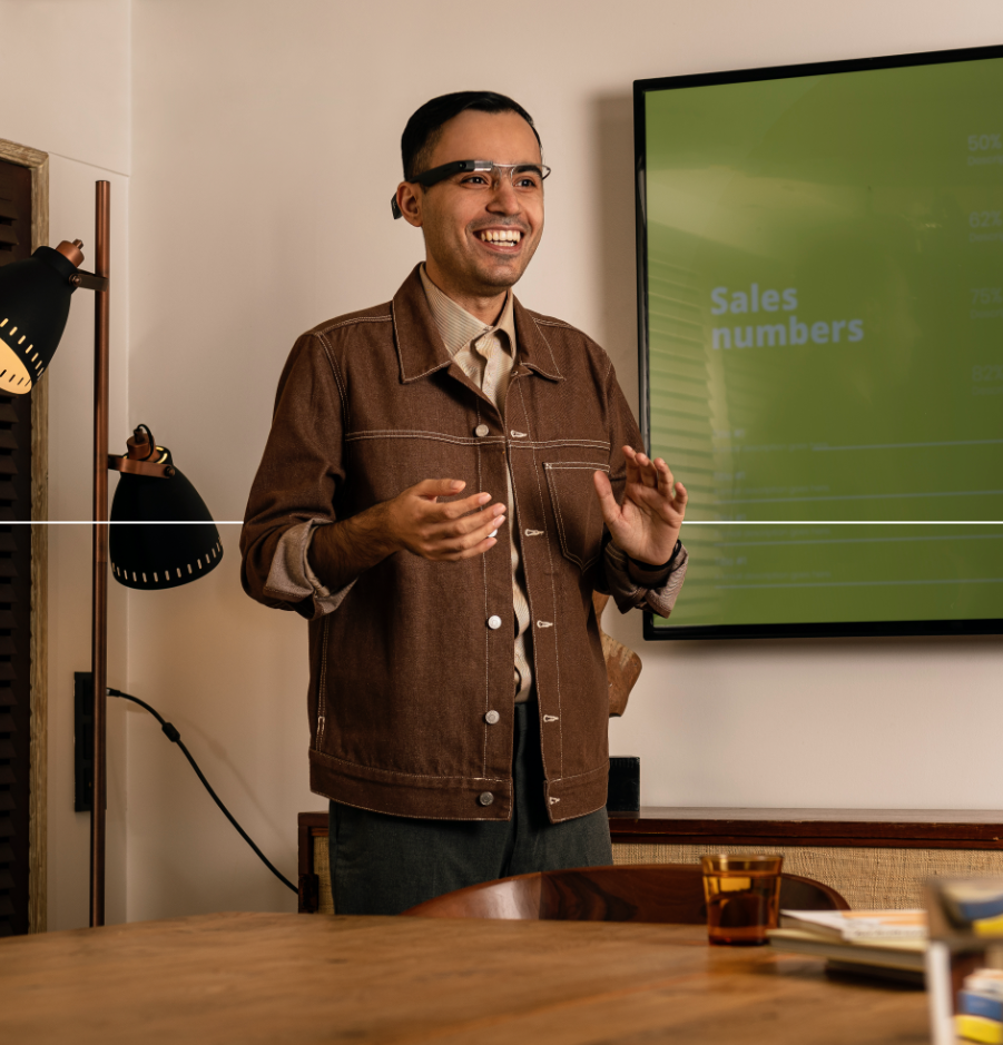 A man standing in front of a presentation screen in a conference room while wearing Envision Glasses