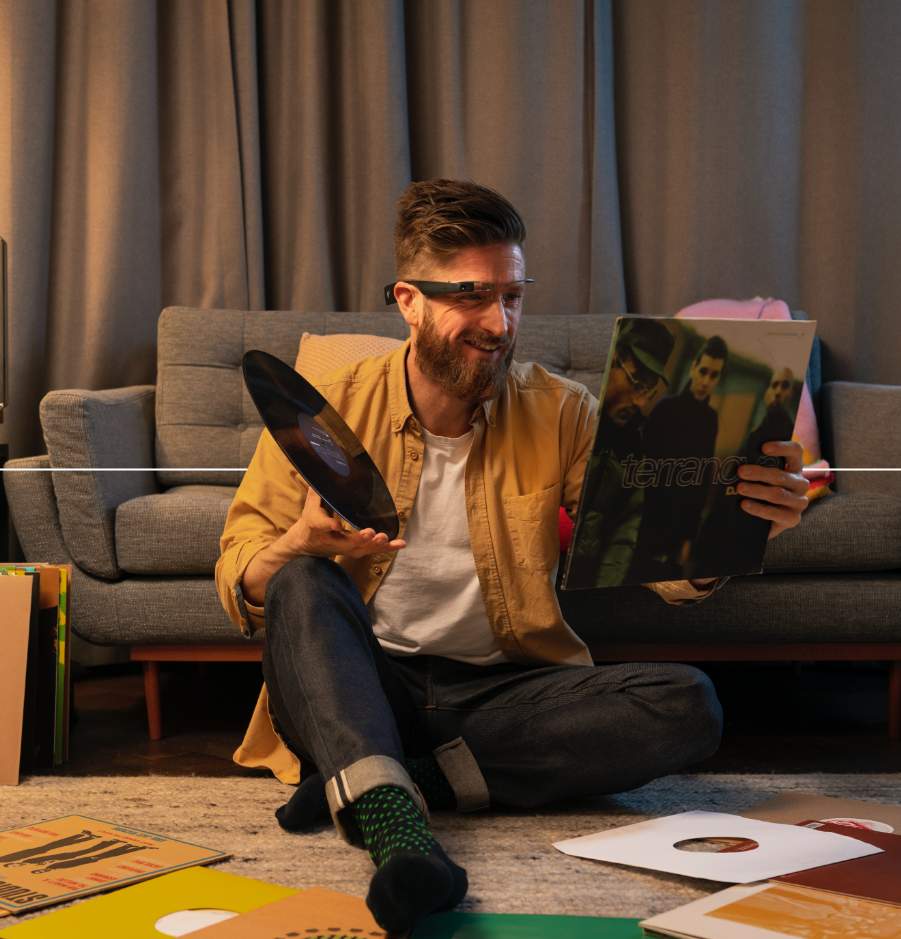 A man, sitting on the floor of a living room, scanning through a bunch of record album covers with Envision Glasses