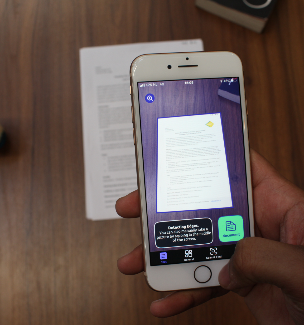 Holding a phone with the right hand. The Envision app is open and a scan of a document is made.