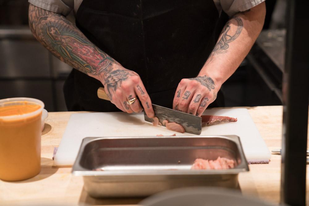 A chef slices pork at Canon in East Sacramento for Visit Sacramento.