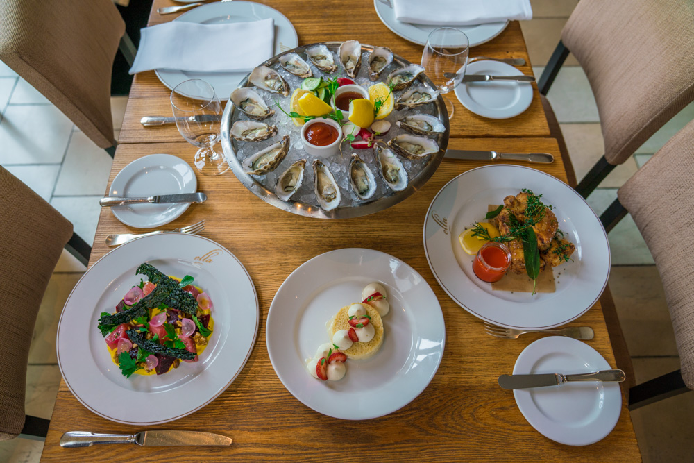 A plate of salad, oysters and dessert sit on a wood table at Ella in Downtown Sacramento for Visit Sacramento.