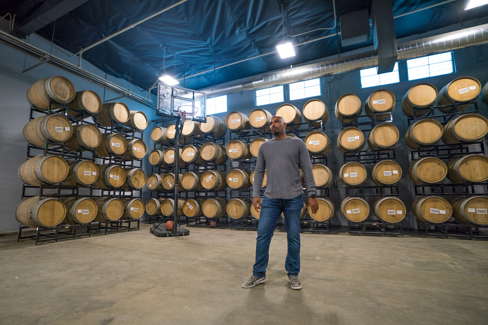 Rob Archie stands in front of casks and smokers at Urban Roots Brewery and Smokehouse in Richmond Grove Sacramento for Visit Sacramento.